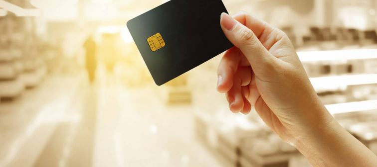 hand holding credit card with blur store background